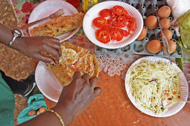 A Rolex, made rolling together a chapati bread with an omelette and various vegetables like sliced tomatoes, onions and cabbage, is Uganda's favorite snack. Picture: AFP/Isaac Kasamani
