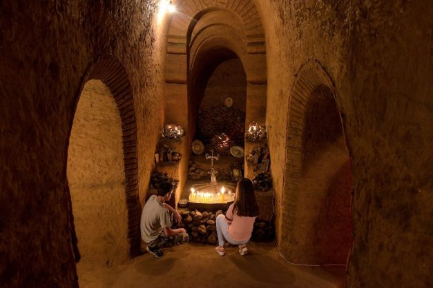 Visitors look at lit candles at an altar, part of a network of subterranean caves and tunnels known as 'Master Levon's divine underground' in the village of Arinj outside the capital Yerevan. Picture: AFP