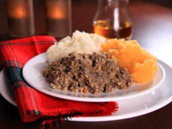Scottish Haggis Serving For A Burns Night Dinner Against A Royal Stuart Tartan