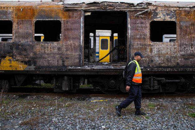 A Metrorail official walks passed a charred train carriage in Cape Town. It is one of several carriages damaged in arson attacks in recent weeks. Archived photo: Ashraf Hendricks