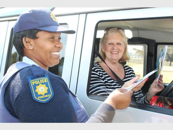 Constable Shumikazi Mbuli giving Lorna Hill some pamphlets during the roadblock.