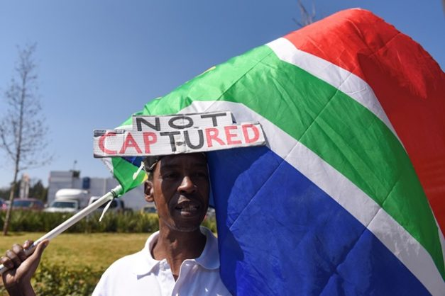 A demonstrator is seen, 20 August 2018, outside the hearings of the Judicial Commission of Inquiry into Allegations of State Capture, Corruption, Fraud in the Public Sector in Parktown. Picture: Refilwe Modise