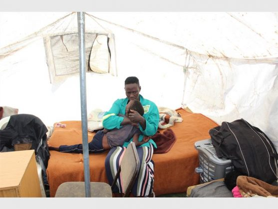 Wendy 'MaButhelezi' Ndaba inside her tent with her disabled son. Photo: Lucky Thusi.