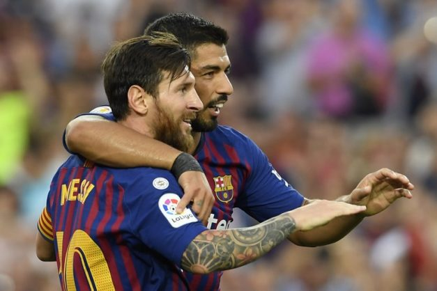 Barcelona's Argentinian forward Lionel Messi (L) celebrates scoring his team's sixth goal with Barcelona's Uruguayan forward Luis Suarez during the Spanish league football match between FC Barcelona and SD Huesca at the Camp Nou stadium in Barcelona on September 2, 2018. / AFP PHOTO / LLUIS GENE