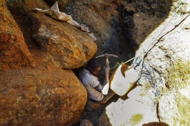 An illegal miner digs between rocks as he searches for precious stones on August 3, 2018, in Nthoro village, on the outskirts of the mining town of Montepuez, Mozambique. The discovery of rubies by a local woodcutter just nine years ago sparked a