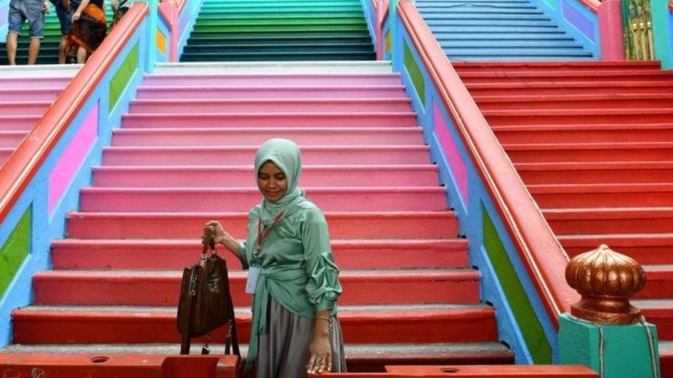 A tourist has her picture taken in front of the newly-painted 272-steps staircase leading to Malaysia's Batu Caves Hindu temple in Kuala Lumpur. Picture: AFP