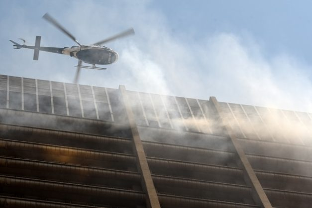 The police helicopter helping remove the stranded firefighters.  The scene of a fire in the Gauteng Department of Health and the Department of Human Settlements building on Sauer street in the Johannesburg CBD, 5 September 2018. The fire broke out on the top floors of the building and spread fast, a fire fighter fell to their death and two others died in the blaze. The police helicopter rescued some stranded firfighters from the roof during the operation. Picture: Neil McCartney