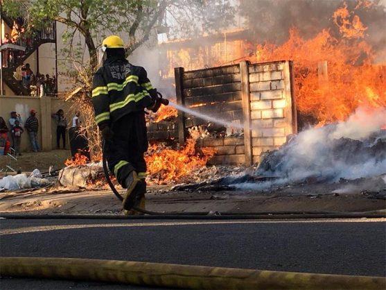 A firefighter battles the flames of the fire at the Courtyard building on Beatrice Street on 2 September. Photo: Warren Myburgh.