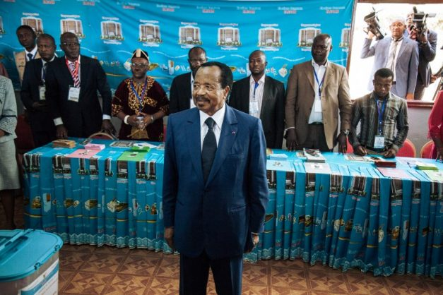 Cameroon's incumbent President Paul Biya (C) looks on as he votes at the polling station in Bastos neighbourhood in the capital Yaounde, on October 7, 2018 during Cameroon's presidential election.  Cameroonians began voting in crunch presidential polls, with octogenarian leader seeking a seventh term against a backdrop of unprecedented violence in the country's English-speaking regions. / AFP PHOTO / ALEXIS HUGUET