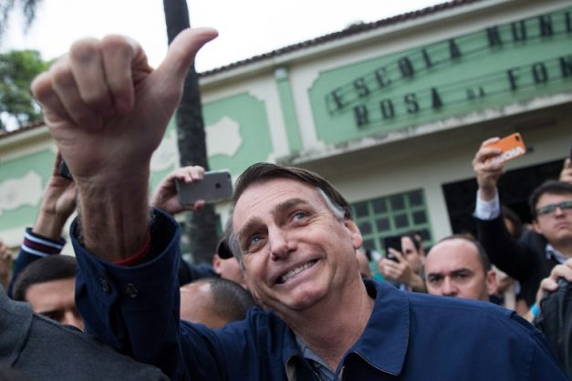 Brazil's right-wing president from the Social Liberal Party (PSL) Jair Bolsonaro gives his thumbs up after casting his vote at Villa Militar, during general elections, in Rio de Janeiro, Brazil, on October 7, 2018. / AFP PHOTO / Fernando Souza