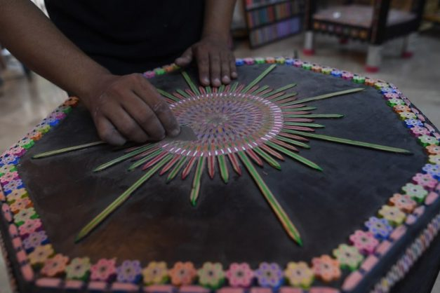 In this photograph taken on October 4, 2018, Pakistani artist Bilal Asif works on his studio in Karachi. - With a sharp eye for detail, Bilal Asif carefully files down pencils in his studio as part of a quest to set a world record for creating the largest swing made from pencil parts. (Photo by ASIF HASSAN / AFP)