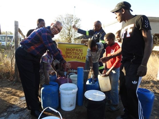 Limpopo Premier Stanley Mathabatha, left, assists thirsty residents of Giyani. They asked Mathabatha to intervene in a payment squabble. Picture: Alex Matlala