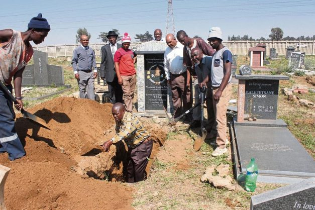 A family digs a grave for reburial over the weekend after they discovered that the employees who were supposed to do the job were on strike. Photo: Lazarus Dithagiso