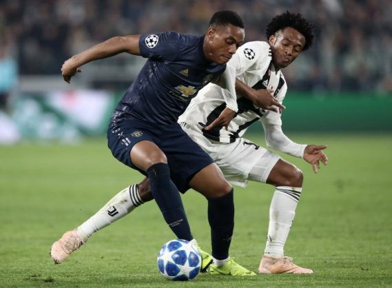 Manchester United's French striker Anthony Martial (L) holds off Juventus' Colombian midfielder Juan Cuadrado during the UEFA Champions League group H football match Juventus vs Manchester United at the Allianz stadium in Turin on November 7, 2018. (Photo by Isabella BONOTTO / AFP)