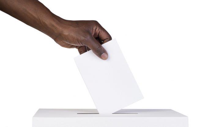 Ballot box with person casting vote on blank voting slip | Image: istock