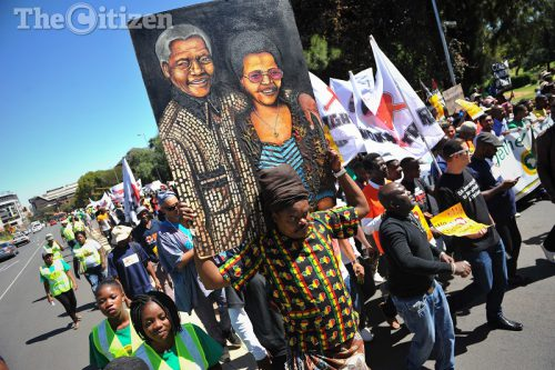 A man attending a protest, alongside hundreds of other protesters, carries a painting of Nelson Mandela and Graca Machel during an anti xenophobia march organised by the African Diaspora Forum in Johannesburg, 28 March 2017. Picture: Michel Bega