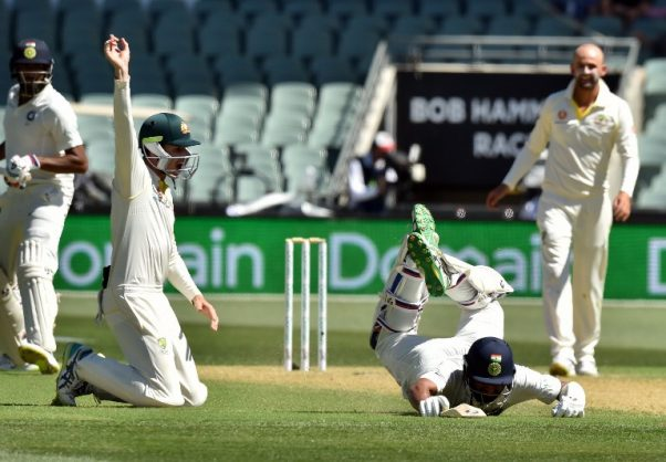 India's batsman Cheteshwar Pujara (C) survives a run out attempt as Australia's fielder  Peter Handscomb (2nd L) looks on during day one of the first cricket Test match at the Adelaide Oval on December 6, 2018. (Photo by PETER PARKS / AFP) / -- IMAGE RESTRICTED TO EDITORIAL USE - STRICTLY NO COMMERCIAL USE --