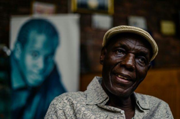 Zimbabwe music icon Oliver 'Tuku' Mtukudzi, pictured in January 2018. Over his shoulder is a portrait of his late son, Sam Mtukudzi. AFP/Jekesai NJIKIZANA