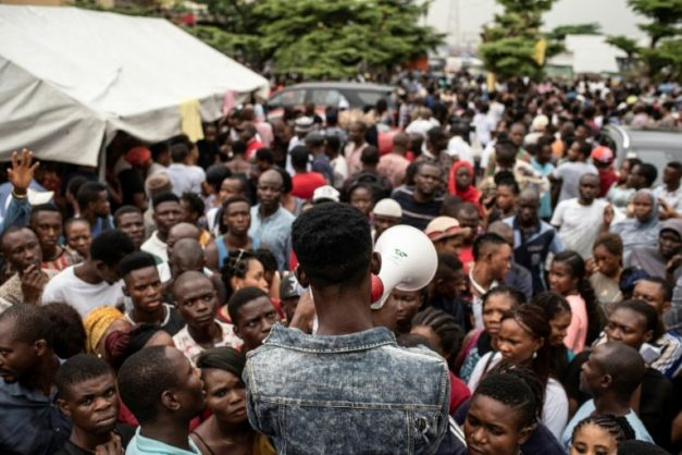 People gathered at one of the Permanent Voter Cards (PVCs) collection points in Lagos listen attentively for names to be called out over a megaphone to receive their card, but many were unable to do so due to logistical snafus. AFP/STEFAN HEUNIS
