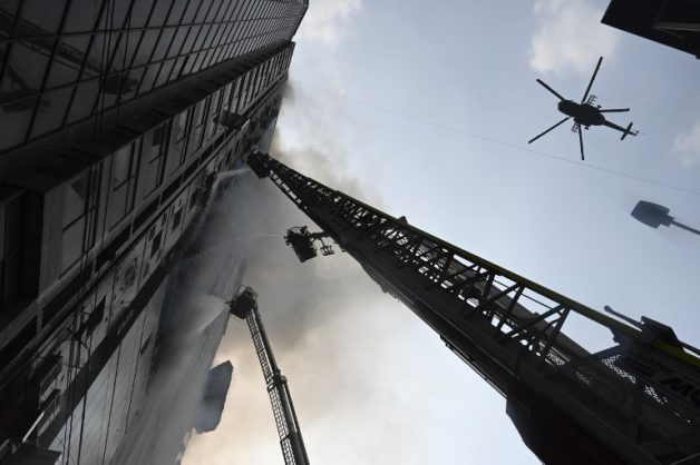 A helicopter carries water to drop on a burning office building as Bangladeshi firefighters on ladders work to extinguish the blaze in Dhaka on March 28, 2019. - A huge fire tore through a Dhaka office block March 28 killing at least five people with many others feared trapped in the latest major inferno to hit the Bangladesh capital. (Photo by MUNIR UZ ZAMAN / AFP)