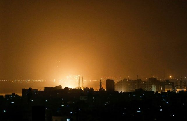 The sky above buildings on the Gaza Strip glows orange during an Israeli air strike in Gaza City late on March 14. AFP/MAHMUD HAMS