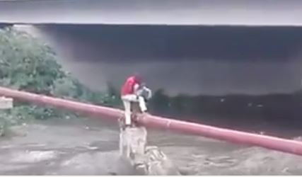 Vincent Cosa saving the boy who was stuck on a pipe above the raging Jukskei River, Johannesburg. Picture: Screenshot from the video