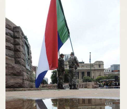 Afrikaners wearing military uniforms carry a Vierkleur flag at the Paul Kruger statue in Church Square, in Pretoria, 8 April 2015, after the statue was vandalised. White Afrikaners gathered to protest against the vandalism and the possible removal of other statues around the country. Picture: Michel Bega