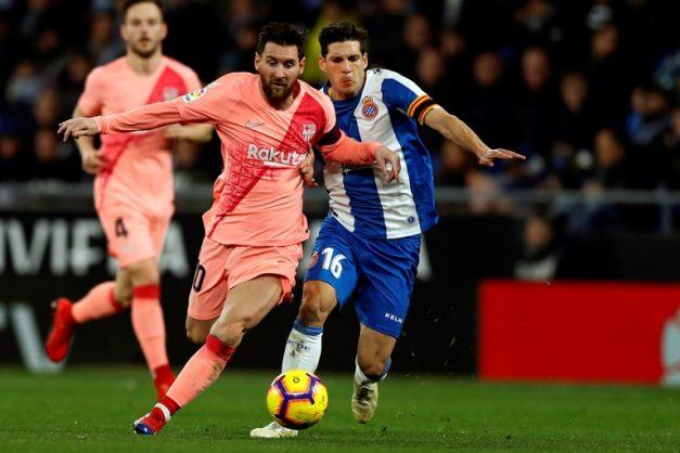 FC Barcelona's Lionel Messi (L) in action against RCD Espanyol's Javi Lopez (R) during a Spanish LaLiga soccer match between RCD Espanyol and FC Barcelona at the Cornella-El Prat stadium in Cornella, Catalonia, north eastern Spain, 08 December 2018.  EPA-EFE/TONI ALBIR