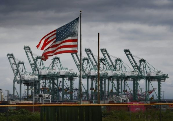 The US flag flies over shipping cranes and containers in Long Beach, California, where a lot of Chinese exports land. AFP/File/Mark RALSTON