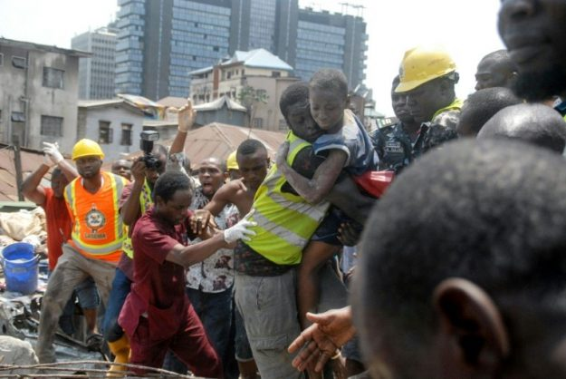 Survivor: Emergency workers pluck a child from the collapsed building. The disaster left 20 dead, according to a new toll . Picture: AFP / SEGUN OGUNFEYITIMI