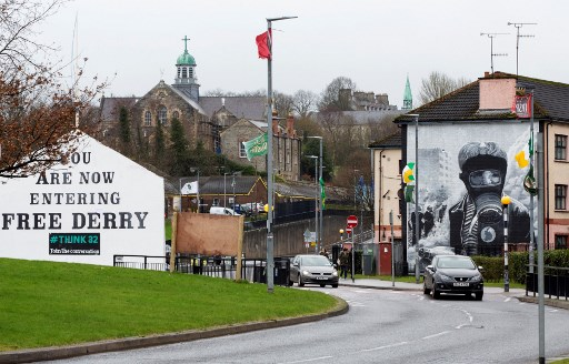 (FILES) In this file photo taken on March 13, 2019 cars pass murals in the Bogside area of Derry, Northern Ireland, on March 13, 2019. A woman has been shot dead during riots in the city of Londonderry in Northern Ireland and the killing is being treated as a terrorist incident, police said on April 19, 2019, following the latest upsurge in violence to shake the troubled region (Photo by Paul FAITH / AFP)