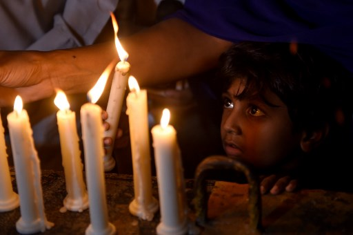 A Pakistani Christian child looks on as adults light candles to pay tribute to Sri Lankan blasts victims in Karachi on April 21, 2019. (Photo by RIZWAN TABASSUM / AFP)