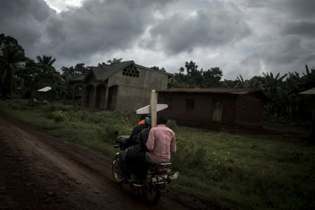 Toll: Three people on a motorbike carry a cross for a grave in Ebola-hit North Kivu . AFP/John WESSELS