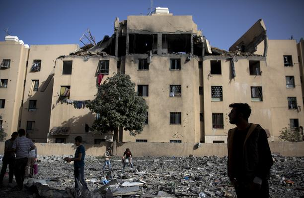 Palestinians inspect the damage of a destroyed house following a late night Israeli missile strike in town of Beit Lahiya, Northern Gaza Strip, Monday, May. 6, 2019. The Israeli military has lifted protective restrictions on residents in southern Israel while Gaza's ruling Hamas militant group reported a cease-fire deal had been reached to end the deadliest fighting between the two sides since a 2014 war. (AP Photo/Khalil Hamra)
