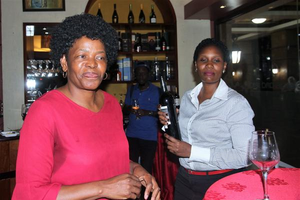 Ugandan businesswoman, Ms Nanyunja Lillian Muleke and the South African winemaker, Ms Rosemary Mosia speaking to wine lovers at the wine-tasting session hosted by Muleke at her La Ville Wines & Spirits shop in Kampala last night. PHOTO: Supplied