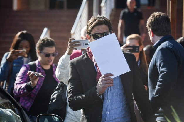 Adam Catzavelos is seen hiding his face behind a sheet of paper as he leaves the Randburg Magistrates Court after appearing for the video captured of him using the k word on a beach in Greece, 28 May 2019, Johannesburg. Picture: Jacques Nelles