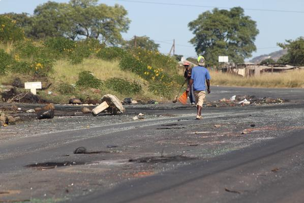Local youths clear debris at the Slangspruit entry point to Imbali Township on Wednesday, one of the areas where Msunduzi residents protested this week. PHOTO: ANA