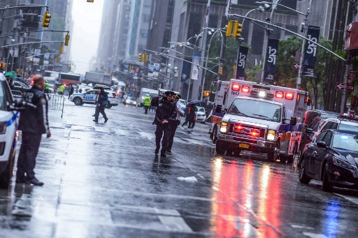 Policemen stand near emergency services vehicles after a helicopter crash-landed on top of a building in midtown Manhattan in New York on June 10, 2019. Picture: Johannes EISELE / AFP