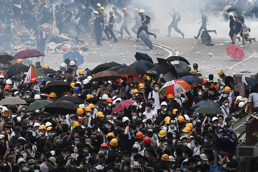 Protesters react after police fired tear gas during a rally against a controversial extradition law proposal in Hong Kong on June 12, 2019. Picture: Anthony WALLACE / AFP