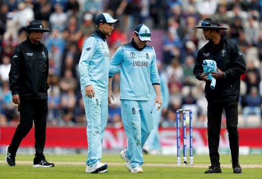 England's captain Eoin Morgan (2R) is assisted by teammate Joe Root (2L) as he walks off the fields with an injury during the 2019 Cricket World Cup group stage match between England and West Indies at the Rose Bowl in Southampton, southern England, on June 14, 2019. (Photo by Adrian DENNIS / AFP) / RESTRICTED TO EDITORIAL USE