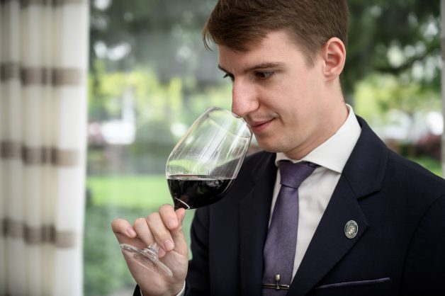 World's best sommelier, 27-year-old Marc Almert smells a glass of red wine  at the two-Michelin-starred Pavillon restaurant at the Baur au Lac hotel in Zurich. (Photo by Fabrice COFFRINI / AFP)