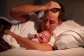 Father Lying In Bed With Crying Baby Daughter
