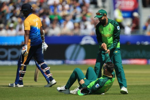 South Africa's Imran Tahir (R) pulls South Africa's captain Faf du Plessis up during the 2019 Cricket World Cup group stage match between Sri Lanka and South Africa at the Riverside Ground, in Chester-le-Street, northeast England, on June 28, 2019. (Photo by Lindsey PARNABY / AFP) / RESTRICTED TO EDITORIAL USE