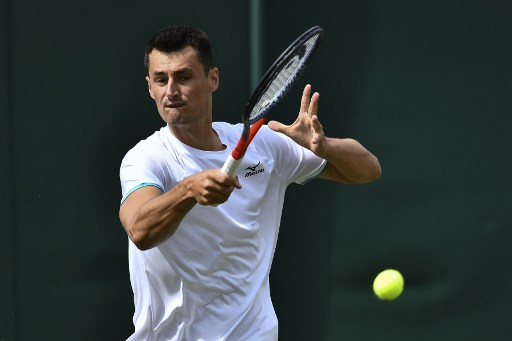 Australia's Bernard Tomic returns against France's Jo-Wilfried Tsonga during their men's singles first round match on the second day of the 2019 Wimbledon Championships at The All England Lawn Tennis Club in Wimbledon, southwest London, on July 2, 2019. (Photo by Ben STANSALL / AFP) / RESTRICTED TO EDITORIAL USE