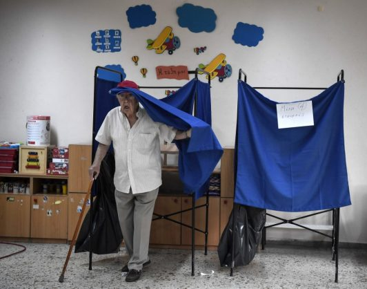 A man steps out of a polling booth to cast his vote at a polling station during general elections in Athens on July 7, 2019. (Photo by Louisa GOULIAMAKI / AFP)