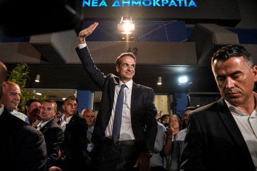 Greece's newly elected Prime Minister and leader of conservative New Democracy party Kyriakos Mitsotakis, waves at his supporters outside the party's headquarters after the official results of the elections, in Athens on July 7, 2019. - Greek Prime Minister Alexis Tsipras conceded defeat in a general election to Kyriakos Mitsotakis, head of the conservative New Democracy party, his office said. Leftist Tsipras called Mitsotakis to congratulate him, a source in the prime minister's office told AFP, with New Democracy on track to score a landslide victory according to early results. (Photo by LOUISA GOULIAMAKI / AFP)