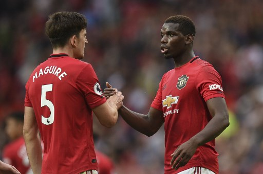Manchester United's English defender Harry Maguire (L) shakes hands with Manchester United's French midfielder Paul Pogba (R) on the pitch at the final whistle in the English Premier League football match between Manchester United and Chelsea at Old Trafford in Manchester, north west England, on August 11, 2019. - Manchester United won the game 4-0. (Photo by Oli SCARFF / AFP) / RESTRICTED TO EDITORIAL USE. No use with unauthorized audio, video, data, fixture lists, club/league logos or 'live' services. Online in-match use limited to 120 images. An additional 40 images may be used in extra time. No video emulation. Social media in-match use limited to 120 images. An additional 40 images may be used in extra time. No use in betting publications, games or single club/league/player publications. /
