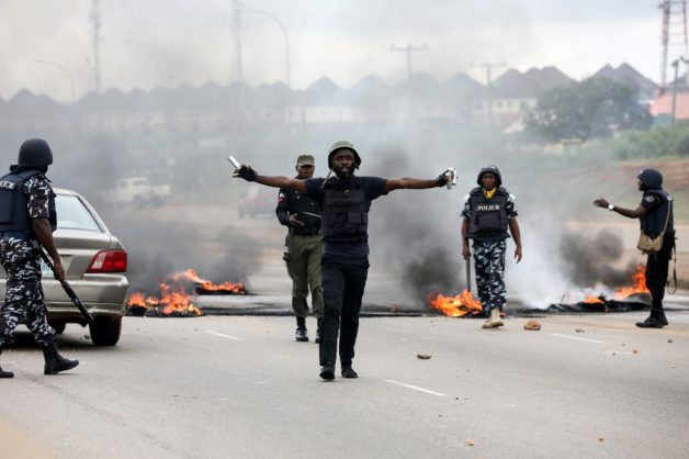Anti-riots policemen try to calm down protestors during a demonstration and attacks against South Africa's owned shops in Abuja, on September 4, 2019. - More than a hundred demonstrators clashed with police near a South African-owned supermarket in the Nigerian capital on September 4, 2019 as resentment simmered over attacks on foreign-owned shops in South Africa. Demonstrators burned tyres and hurled rocks outside a mall in Abuja where a branch of the Shoprite supermarket is located, before being repelled by a dozen police, an AFP journalist saw. (Photo by KOLA SULAIMON / AFP)
