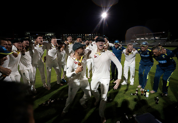 Nathan Lyon and Steve Smith of Australia celebrate with team mates while singing the team song on the pitch after Australia claimed victory to retain the Ashes during day five of the 4th Specsavers Test between England and Australia at Old Trafford on September 08, 2019 in Manchester, England. (Photo by Ryan Pierse/Getty Images)