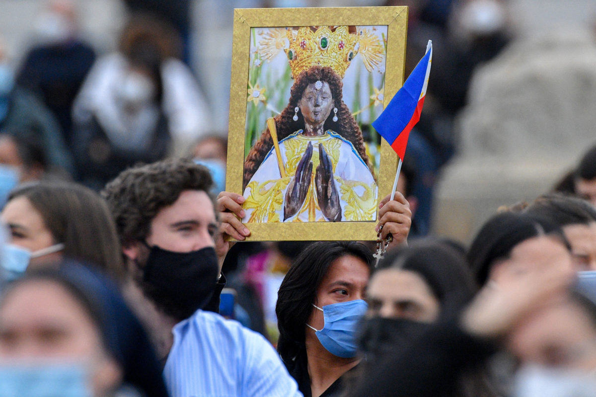 A Philippine attendee holds a picture of Our Lady of the Philippines, and the Philippine flag during the Pope's weekly Angelus prayer on March 14, 2021 at St. Peter's Square in The Vatican. (Photo by Tiziana FABI / AFP)